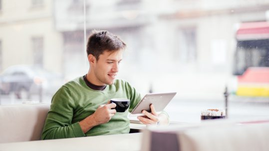 Young man drinking coffee in cafe and using tablet computer